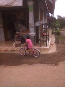 anak kecil bersepeda memakai helm